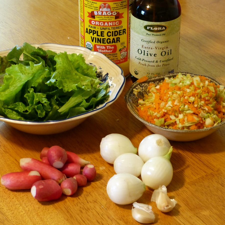 Various greens, chopped cabbage and carrot, radishes, onions, garlic and oil and vinegar.